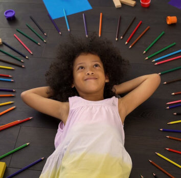 little girl lying with her pencils